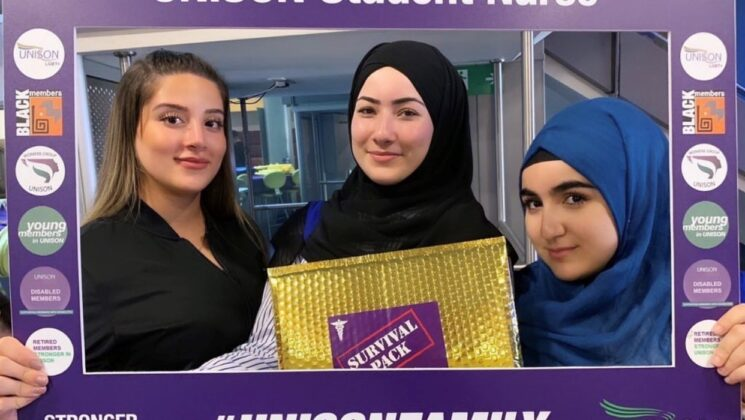 Three Student Nurses hold up a UNISON branded selfie-board